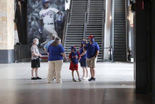 Baseball fans check out the concourse at Globe Life Field, the new home of the Texas Rangers baseball team, during the first day of public tours Monday, June 1, 2020, in Arlington, Texas. As lock-downs are lifted, restrictions on social gatherings eased and life begins to resemble some sense, sports are finally starting to emerge from the coronavirus pandemic. Major League Soccer, the NBA and NHL have agreements in place to restart their seasons, and baseball is going through contentious rounds of negotiations over what it might take for umpires to cry Play Ball! and America's pastime to provide a weary public some much-needed entertainment.(AP Photo/LM Otero, File)