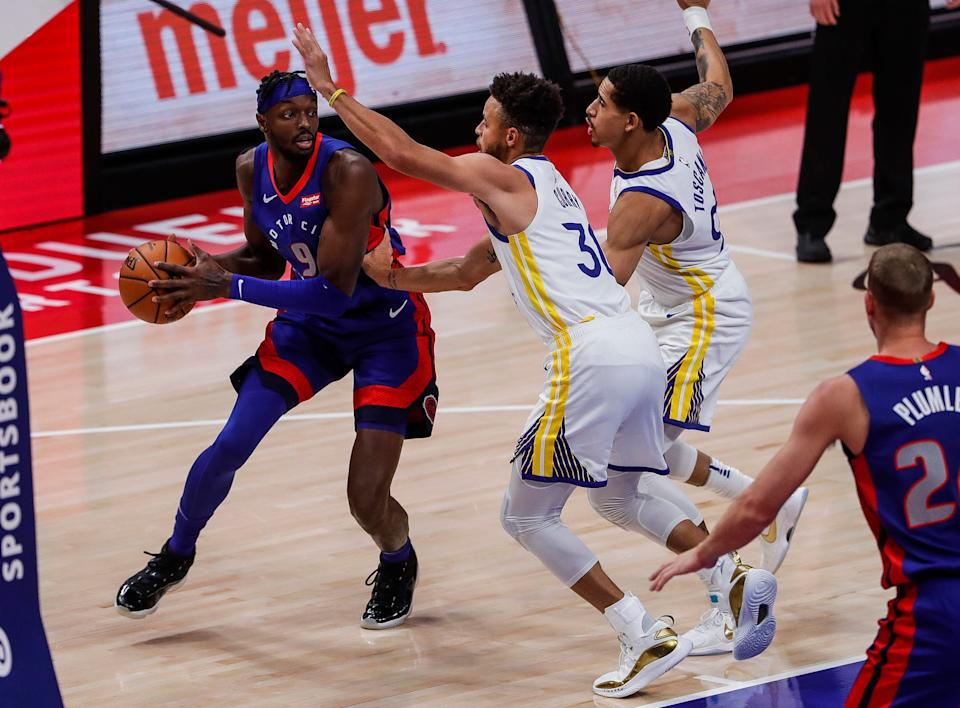 Pistons forward Jerami Grant looks to pass around Warriors guard Stephen Curry during the first half at Little Caesars Arena on Tuesday, Dec. 29, 2020.