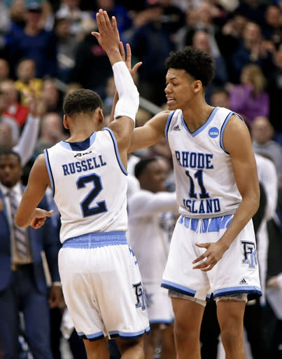 FILE - In this Thursday, March 15, 2018, file photo, Rhode Island's Jeff Dowtin (11) greets Fatts Russell during overtime in a first-round game against Oklahoma at the NCAA men's college basketball tournament in Pittsburgh. Dotwin started wearing his shorts short during high school. Dotwin, whose team plays Duke in the second round on Saturday, says he wanted to make it his signature look but endures his fair share of good-natured taunts from opposing student sections. (AP Photo/Keith Srakocic, File)