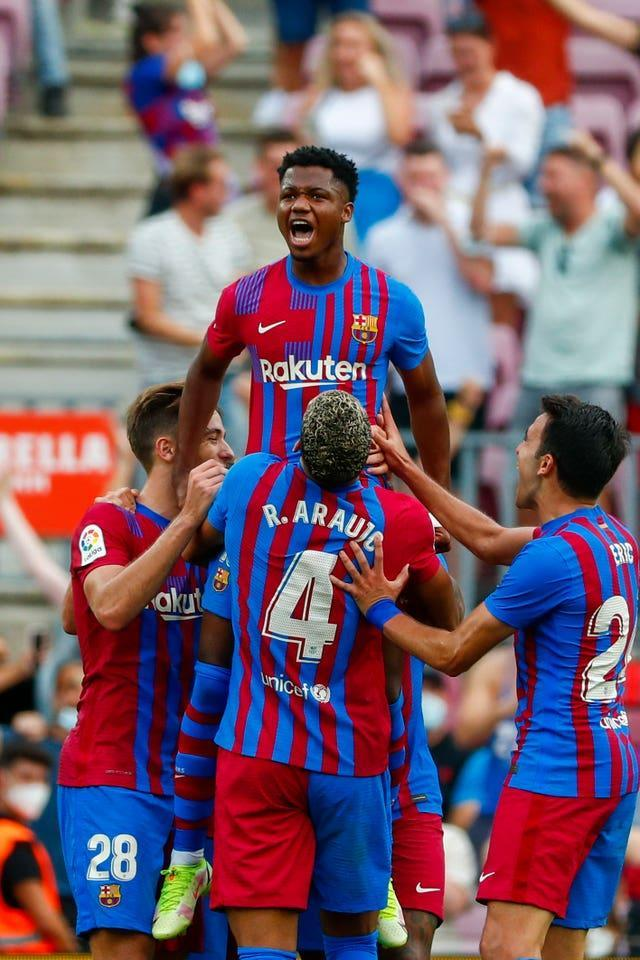 Ansu Fati is held aloft by his Barcelona team-mates after scoring on his return from injury
