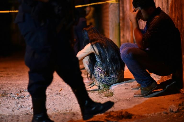 Relatives and friends sit in shock outside the venue of a party where unidentified gunmen killed 13 people in Mexico