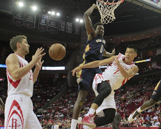 Houston Rockets guard Jeremy Lin, right, makes a pass to teammate Chandler Parsons, left, as he is driven out of bounds by New Orleans Pelicans forward Al-Farouq Aminu (0) during the first half of a preseason NBA basketball game in Houston, Saturday, Oct. 5, 2013. (AP Photo/Richard Carson)