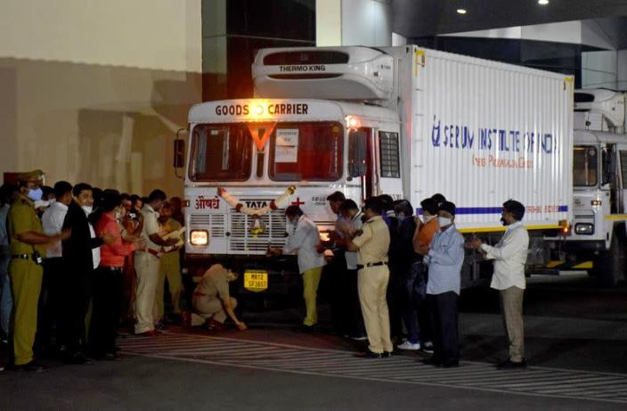 A police officer performs prayers in front of a truck carrying first consignment of COVISHIELD before it leaves from Serum Bio-Pharma Park of Serum Institute of India, for its distribution, in Pune