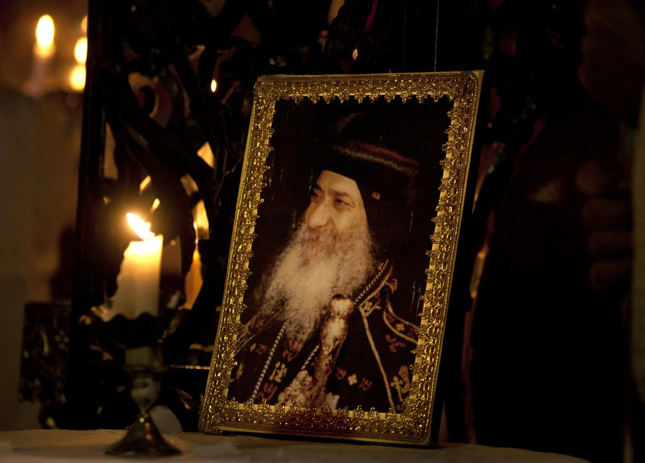 A picture of Pope Shenouda III, the patriarch of the Coptic Orthodox Church is seen during a Sunday mass at the Church of the Holy Sepulchre, traditionally believed by many Christians to be the site of the crucifixion and burial of Jesus Christ, in Jerusalem's Old city, Sunday, March 18, 2012. Pope Shenouda III, the patriarch of the Coptic Orthodox Church who led Egypt's Christian minority for 40 years during a time of increasing tensions with Muslims, died Saturday, aged 88. (AP Photo/Sebastian Scheiner)