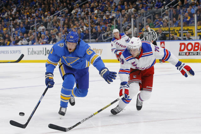 St. Louis Blues' Jacob de la Rose, left, of Sweden, and New York Rangers' Brady Skjei reach for a loose puck during the second period of an NHL hockey game Saturday, Jan. 11, 2020, in St. Louis. (AP Photo/Billy Hurst)