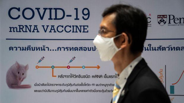 A man wearing a face mask stands next to a board showing the progress of developing an mRNA type vaccine candidate for the coronavirus disease