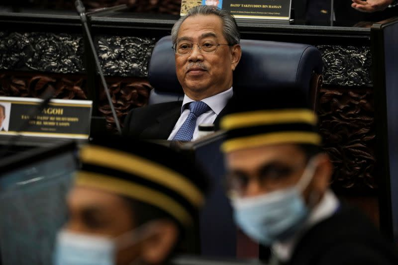 FILE PHOTO: Malaysia's Prime Minister Muhyiddin Yassin reacts during a session of the lower house of parliament, in Kuala Lumpur