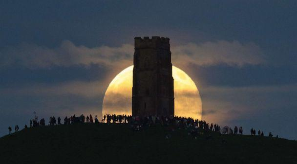 PHOTO: In this June 20, 2016, file photo, a strawberry moon rises behind Glastonbury Tor as people gather to celebrate the summer solstice in Somerset, England. (Matt Cardy/Getty Images, FILE)