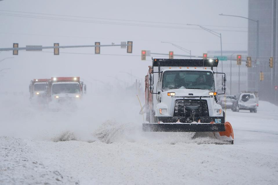 Snowplows works to clear the road during a winter storm Sunday, Feb. 14, 2021, in Oklahoma City. Snow and ice blanketed large swaths of the U.S. on Sunday, prompting canceled flights, making driving perilous and reaching into areas as far south as Texas' Gulf Coast, where snow and sleet were expected overnight.