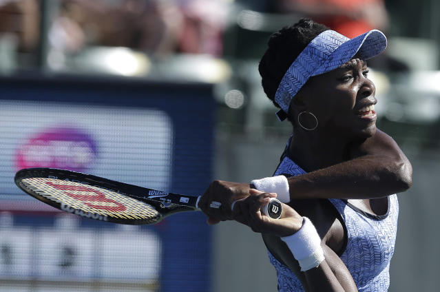 Venus Williams, of the United States, returns the ball to Andrea Petkovic, from Germany, during the second set of their match in the Bank of the West Classic tennis tournament in Stanford, Calif., Friday, Aug. 1, 2014. Petkovic won 6-1, 3-6, 7-5. (AP Photo/Jeff Chiu)