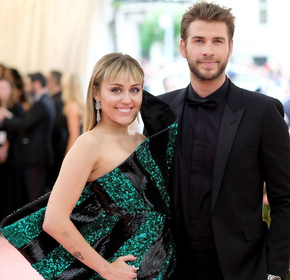 """<p>In November 2015, about two years after ending their engagement, the pair sparked reconciliation rumors when Cyrus helped Hemsworth <a href=""""https://www.instagram.com/p/-FB7wsyypO/"""" rel=""""nofollow noopener"""" target=""""_blank"""" data-ylk=""""slk:adopt a dog"""" class=""""link rapid-noclick-resp"""">adopt a dog</a>. At the start of 2016, Cyrus was spotted wearing her Neil Lane engagement ring again. <em><a href=""""https://people.com/celebrity/miley-cyrus-is-beyond-happy-to-be-engaged-to-liam-hemsworth-again/"""" rel=""""nofollow noopener"""" target=""""_blank"""" data-ylk=""""slk:People"""" class=""""link rapid-noclick-resp"""">People</a> </em>officially reported that the couple was back together on January 21. """"Miley is beyond happy to be engaged to Liam again,"""" a Cyrus source told the outlet. """"It might seem sudden, but they have been very close for the past few months."""" In November 2018, the couple shared heartache after damage to their Malibu home following the California wildfires. A source told <em><a href=""""https://people.com/music/miley-cyrus-marries-liam-hemsworth-why-now/"""" rel=""""nofollow noopener"""" target=""""_blank"""" data-ylk=""""slk:People"""" class=""""link rapid-noclick-resp"""">People</a> </em>that the couple originally intended to wed in their Malibu home. Instead, they got hitched on December 23 in Cyrus's Tennessee home in front of an intimate group. </p>"""