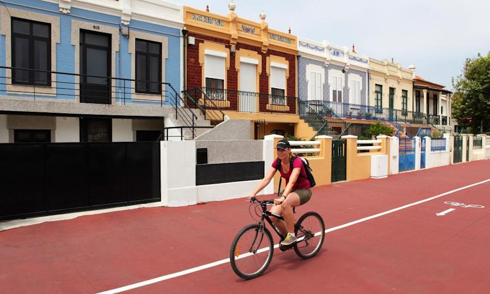 A woman cycles on a cycle-path at Espinho in Portugal.