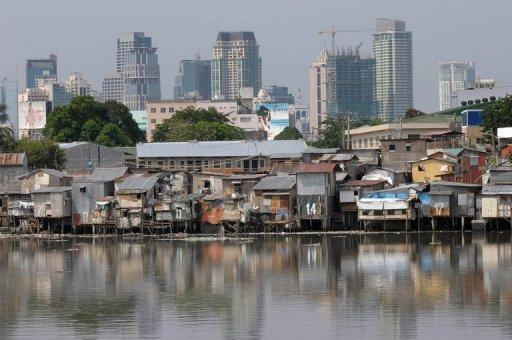 A slum area is backdropped with the Manila skyline
