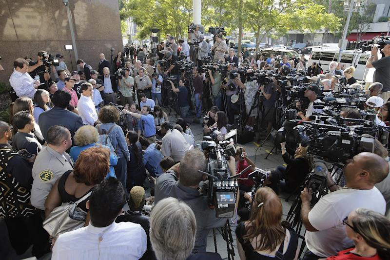 CORRECTS NAME TO GREGG BARDEN, INSTEAD OF GREG BARDEN Jury foreman Gregg Barden, left in white shirt, talks to reporters in the interview area outside a courthouse on Wednesday, Oct. 2, 2013, in Los Angeles, after a jury cleared AEG Live of negligence in a case that attempted to link the death of Michael Jackson to the company that promoted his ill-fated comeback shows. (AP Photo/Jae C. Hong)