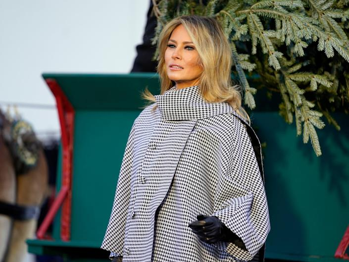 First lady Melania Trump stands next to the 2020 Official White House Christmas tree as it is presented on the North Portico of the White House, Monday 23 November 2020, in Washington ((Associated Press))
