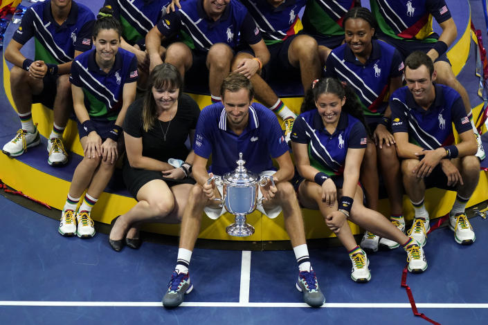 Daniil Medvedev, of Russia, poses for photos with court attendants after defeating Novak Djokovic, of Serbia, in the men's singles final of the US Open tennis championships, Sunday, Sept. 12, 2021, in New York. (AP Photo/Seth Wenig)