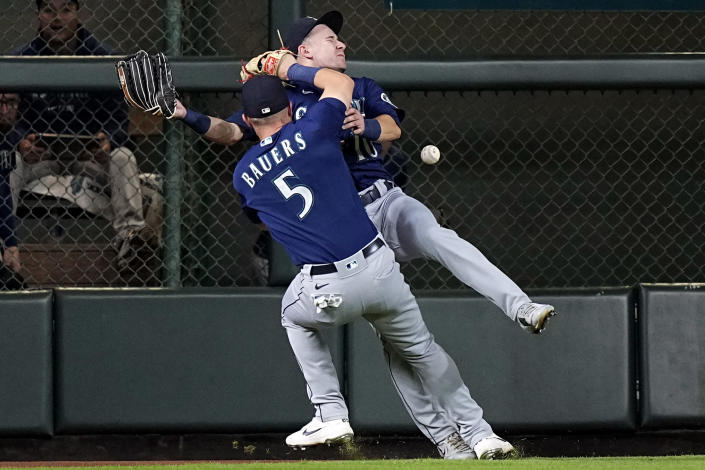 Seattle Mariners left fielder Jake Bauers (5) collides with center fielder Jarred Kelenic (10) while trying to catch a fly ball by Houston Astros' Michael Brantley during the fifth inning of a baseball game Tuesday, Sept. 7, 2021, in Houston. Kelenic was charged with an error on the play. (AP Photo/David J. Phillip)