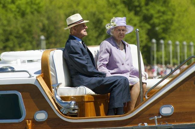 The Queen and the Duke of Edinburgh ride on an Australian Navy barge during a trip on Lake Burley Griffin in Canberra (Arthur Edwards/The Sun/PA)