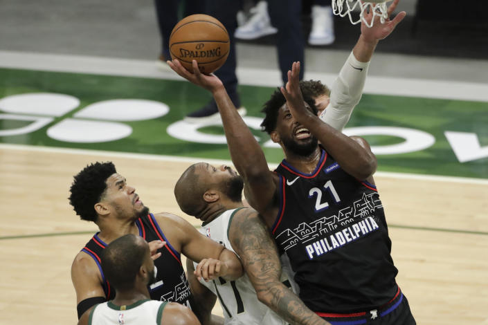 Philadelphia 76ers' Joel Embiid (21) is fouled as he shoots against multiple Milwaukee Bucks' defenders during the second half of an NBA basketball game Thursday, April 22, 2021, in Milwaukee. (AP Photo/Aaron Gash)