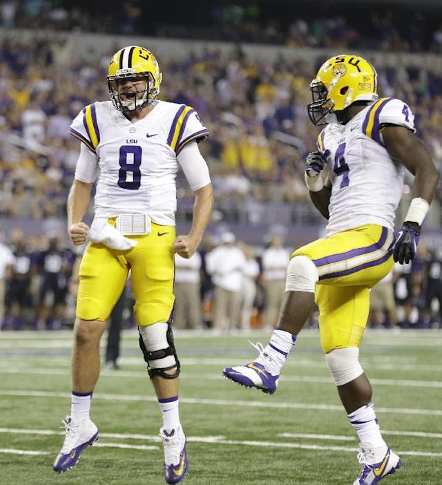 LSU quarterback Zach Mettenberger (8) celebrates a touchdown with teammate running back Alfred Blue (4) during the first half of an NCAA college football game against TCU, Saturday, Aug. 31, 2013, in Arlington, Texas. LSU's J.C. Copeland scored on the play. (AP Photo/LM Otero)