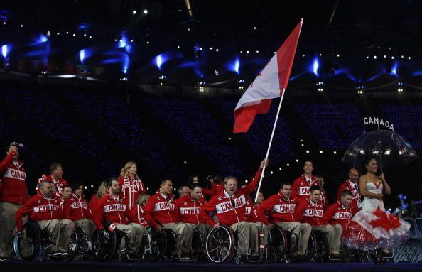 LONDON, ENGLAND - AUGUST 29: Wheelchair Rugby player Garrett Hichling of Canada carries the flag during the Opening Ceremony of the London 2012 Paralympics at the Olympic Stadium on August 29, 2012 in London, England. (Photo by Clive Rose/Getty Images)