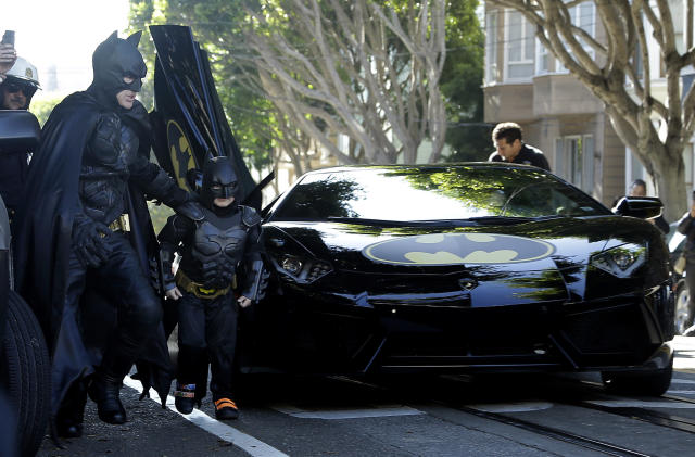 """Miles Scott, dressed as Batkid, second from left, exits the Batmobile with Batman to save a damsel in distress in San Francisco, Friday, Nov. 15, 2013. San Francisco turned into Gotham City on Friday, as city officials helped fulfill Scott's wish to be """"Batkid."""" Scott, a leukemia patient from Tulelake in far Northern California, was called into service on Friday morning by San Francisco Police Chief Greg Suhr to help fight crime, The Greater Bay Area Make-A-Wish Foundation says. (AP Photo/Jeff Chiu)"""