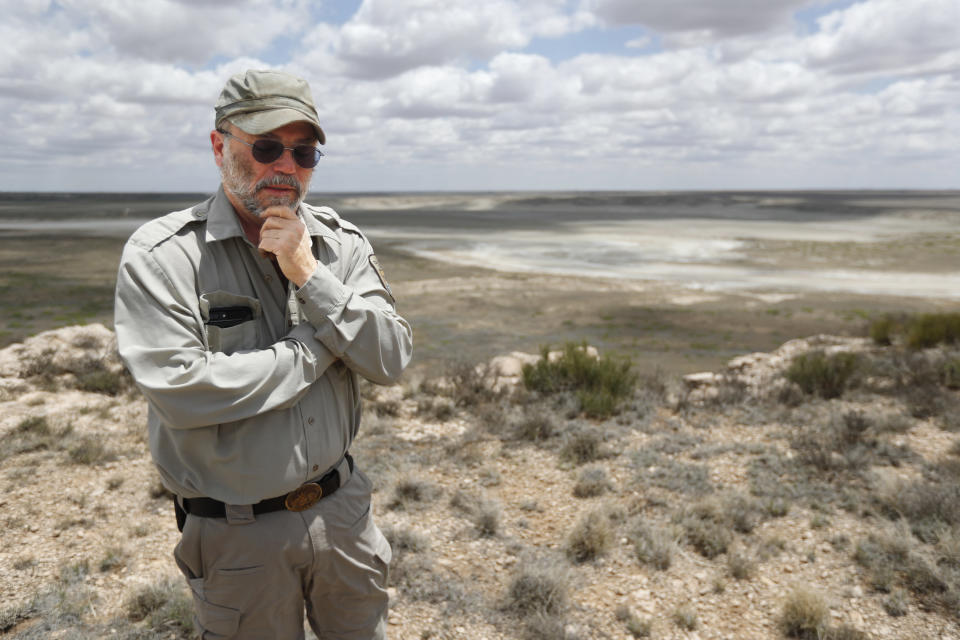 Biologist Jude Smith stands on a bluff overlooking an empty saline lake at the Muleshoe National Wildlife Refuge outside Muleshoe, Texas, on Tuesday, May 18, 2021. The lake is fed by the Ogallala Aquifer, which has been become increasingly dry because of irrigation and drought. (AP Photo/Mark Rogers)