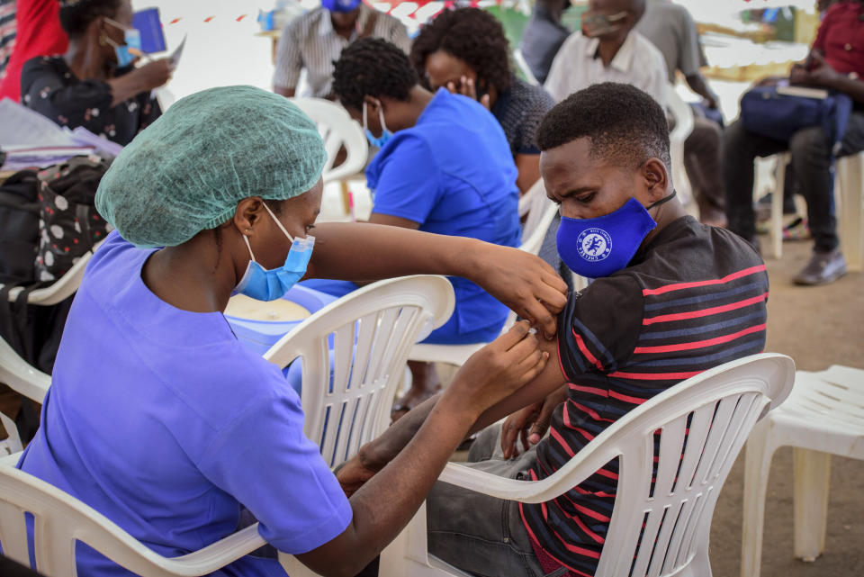 A nurse administers a coronavirus vaccination to a patient at a streetside vaccination tent in downtown Kampala, Uganda Tuesday, Sept. 7, 2021. Uganda is accelerating its vaccination drive in order to administer 128,000 doses that recently arrived and expire at the end of September. (AP Photo/Nicholas Bamulanzeki)
