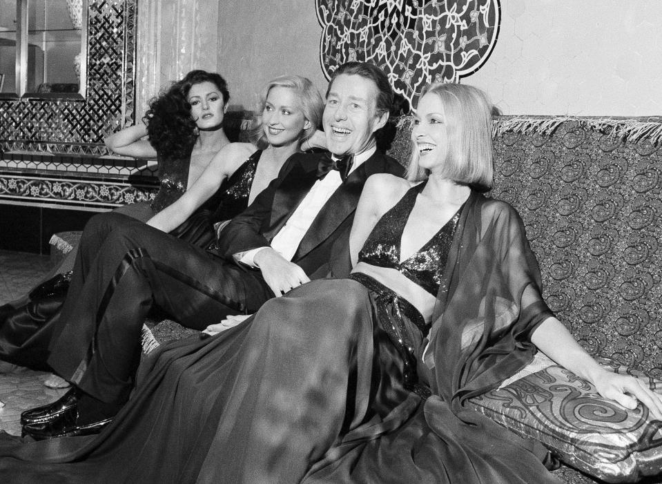 """FILE - Designer Halston laughs with three of his models at the Iranian Embassy in Washington prior to the start of a benefit fashion show on on Oct. 5, 1977. A new series about the fashion designer, """"Halston,"""" premieres Friday on Netflix. (AP Photo/Charles Harrity, File)"""