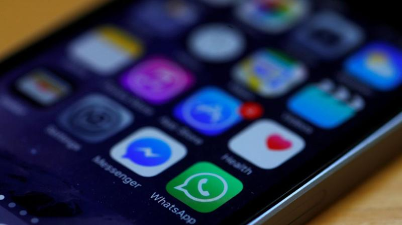 WhatsApp and Facebook messenger icons are seen on an iPhone