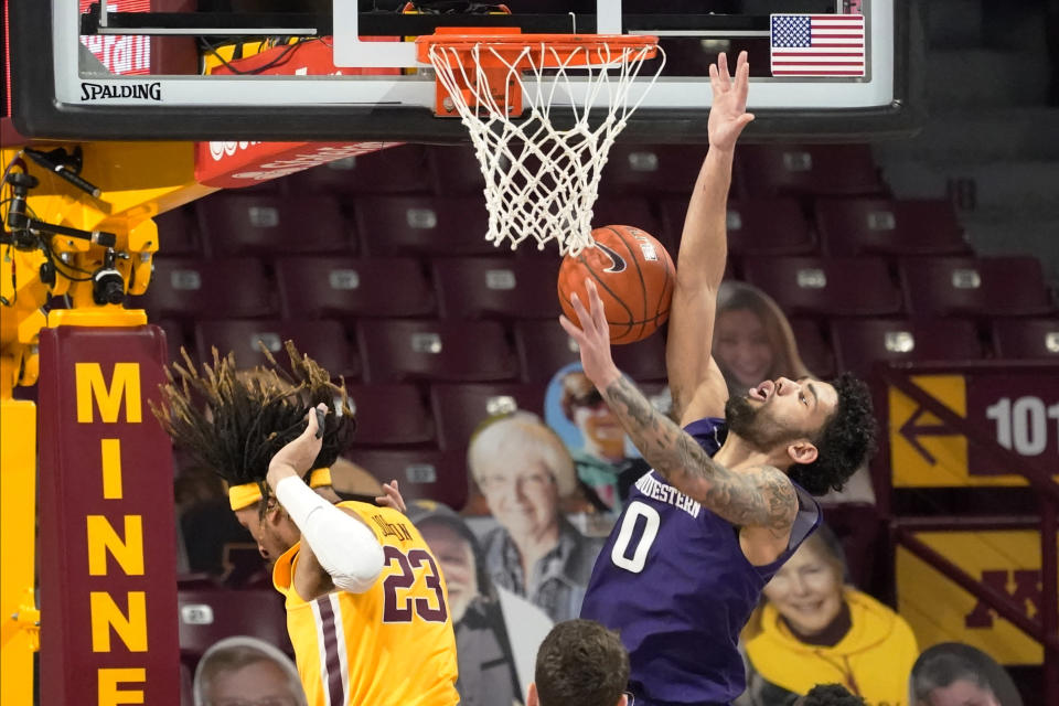 Northwestern's Boo Buie (0) is fouled on a shot-attempt as Minnesota's Brandon Johnson (23) moves away in the first half of an NCAA college basketball game, Thursday, Feb. 25, 2021, in Minneapolis. (AP Photo/Jim Mone)