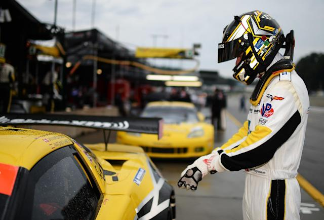 Jan Magnussen, of Denmark, prepares to get in his car during the warm up session for the American Le Mans Series' Petit Le Mans auto race at Road Atlanta, Saturday, Oct. 19, 2013, in Braselton, Ga. (AP Photo/Rainier Ehrhardt)