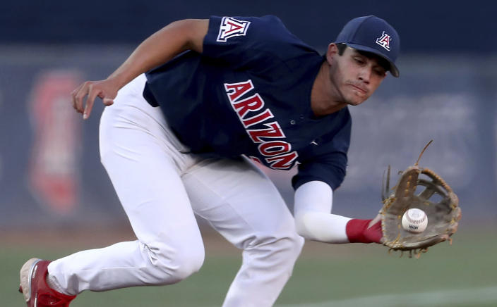 Arizona third baseman Tony Bullard (3) snares a looping liner by Mississippi's Peyton Chatagnier (1) during the first inning of an NCAA college baseball tournament super regional game Saturday, June 12, 2021, in Tucson, Ariz. (Kelly Presnell/Arizona Daily Star via AP)