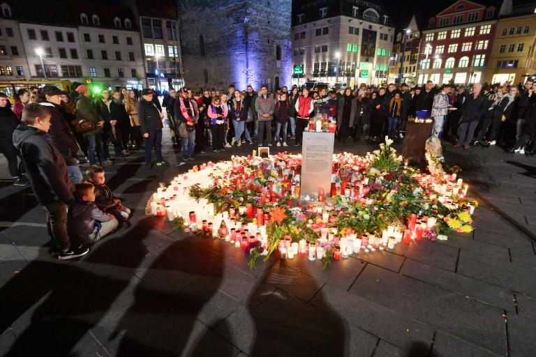 Mourners paid their respects to the victims at a makeshift memorial of flowers and candles at the market square in Halle the day after the attack