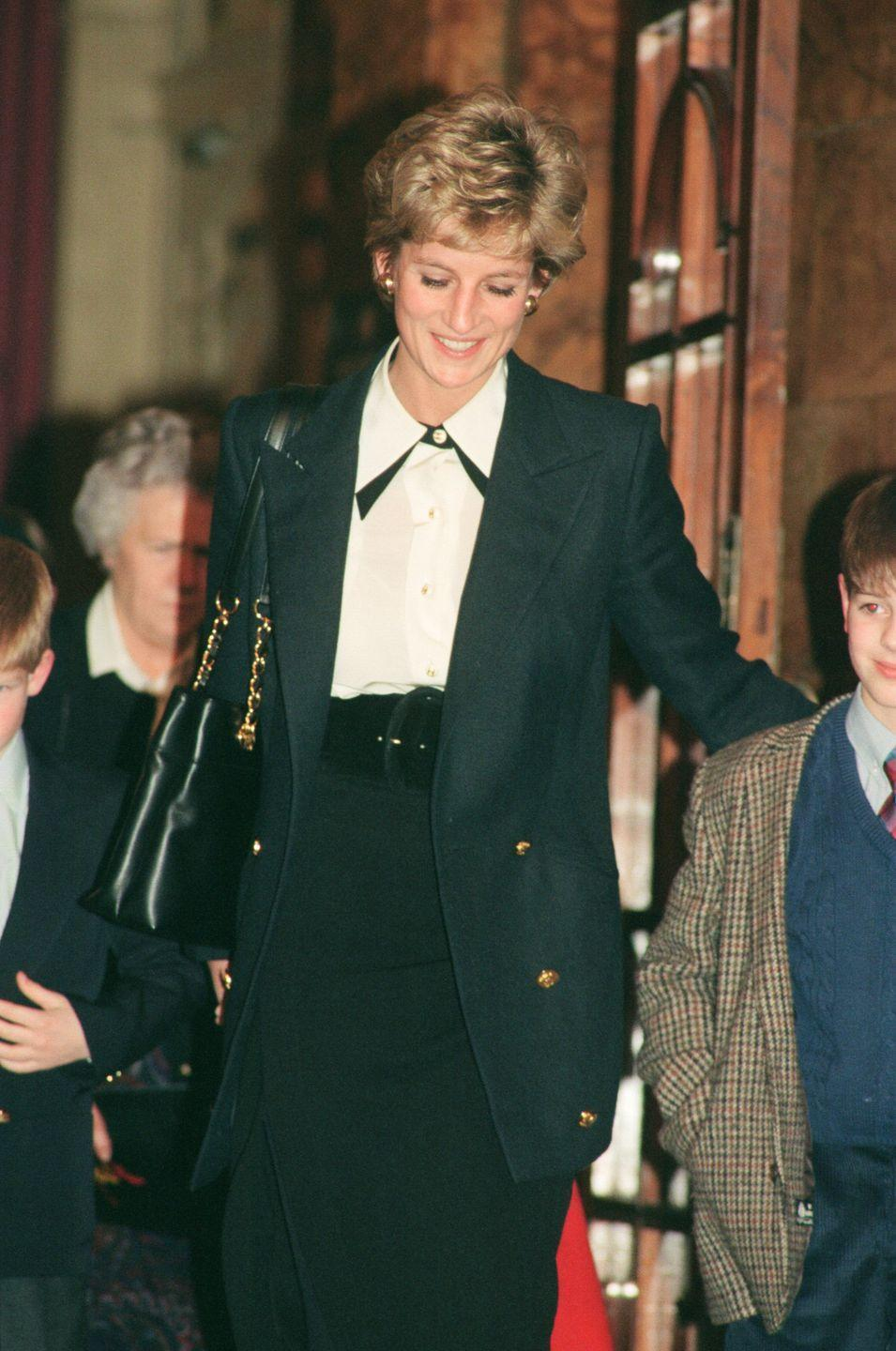 <p>A high-waisted belted skirt adds a feminine touch to Diana's oxford and hunter green suit. </p>