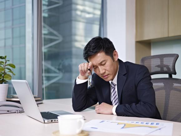 A business person near a computer thinking hard.