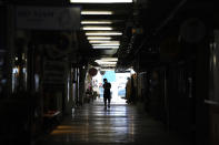 A person walks through closed shops in Siam Square, a famous shopping district in Bangkok, Thailand on Aug. 3, 2021. As Thailand battles a punishing COVID-19 surge with nearly 20,000 new cases every day, people who depend on tourism struggle in what was one of the most-visited cities in the world, with 20 million visitors in the year before the pandemic. (AP Photo/Sakchai Lalit)