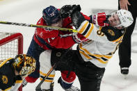 Washington Capitals left wing Conor Sheary (73) and Boston Bruins defenseman Mike Reilly (6) scuffle during the first period of Game 2 of an NHL hockey Stanley Cup first-round playoff series Monday, May 17, 2021, in Washington. (AP Photo/Alex Brandon)