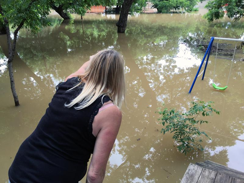 "Lori Grantham of Horseshoe Bend points to flooded homes where residents are staying put. ""Some people refuse to leave,"" she said. (Yahoo News/Jason Sickles)"