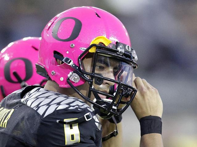Oregon quarterback Marcus Mariota adjusts the strap on his helmet before an NCAA college football game against Washington State in Eugene, Ore., Saturday, Oct. 19, 2013. (AP Photo/Don Ryan)