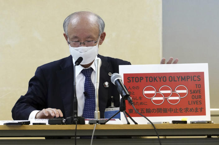 Lawyer Kenji Utsunomiya, a representative of an anti-Olympics group, shows an anti-Olympic banner during a press conference after submitting a petition to the Tokyo government calling for the cancellation of the Tokyo 2020 Olympics and Paralympics. An online petition calling for the Tokyo Olympics to be cancelled has been submitted to the Tokyo government with over 350,000 signatures on Friday morning. The rollout of the petition comes with Tokyo, Osaka and several other areas under a state of emergency with coronavirus infections rising - particularly new variants. (AP Photo/Eugene Hoshiko)