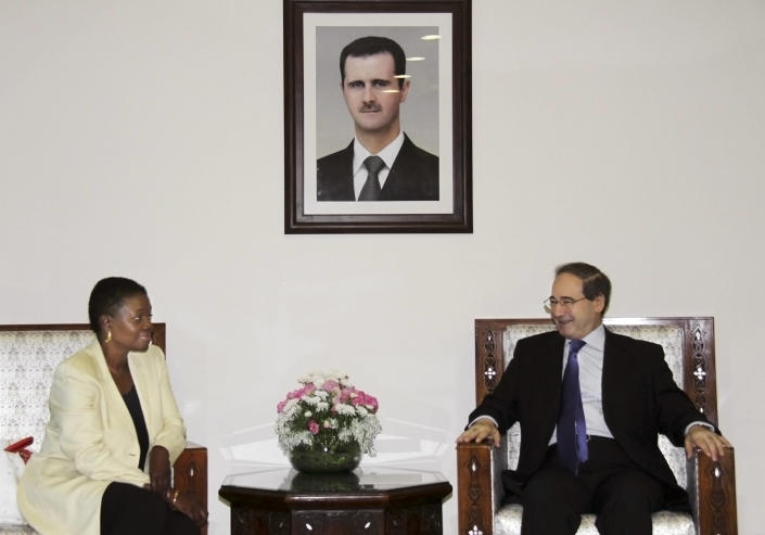UN Under-Secretary-General for Humanitarian Affairs and Emergency Relief Coordinator, Valerie Amos, left, meets with Faisal Mekdad Syrian Ambassador to United Nations, during a press conference in Damascus, Syria, Tuesday, Aug. 14, 2012. The portrait shows Syrian President Bashar Assad. (AP Photo/Bassem Tellawi)