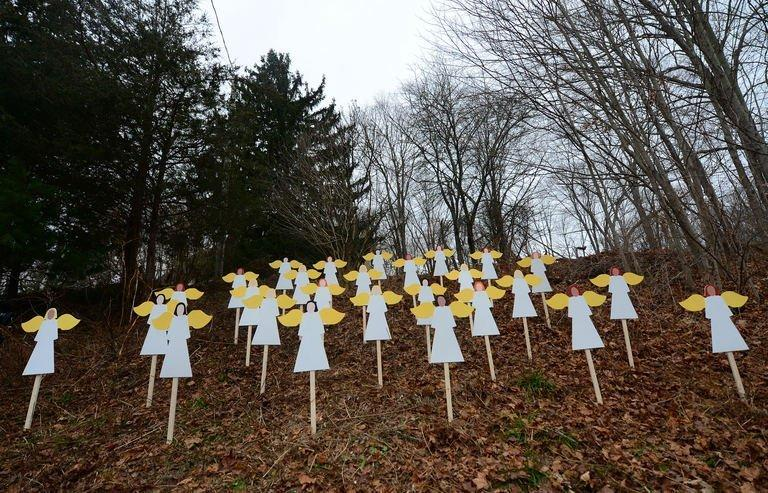 Wooden angel cut-outs are set up on hillside in memory to the victims of a school shooting in Newtown, Connecticut, on December 16, 2012. President Barack Obama has vowed to battle gun violence, casting the fight as a nation's duty to protect its young, as the Connecticut town of Newtown prepared to bury the first two victims of last week's rampage at an elementary school