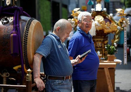 FILE PHOTO: A man uses his smartphone next to a Japanese traditional Taiko drum during the preprartion for the upcoming Kanda festival in Tokyo