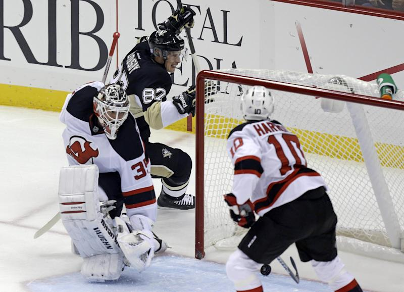 Pittsburgh Penguins center Sidney Crosby (87) celebrates after getting the puck behind New Jersey Devils goalie Cory Schneider (35) for a first-period goal during an NHL hockey game in Pittsburgh on Thursday, Oct. 3, 2013. (AP Photo/Gene J. Puskar)