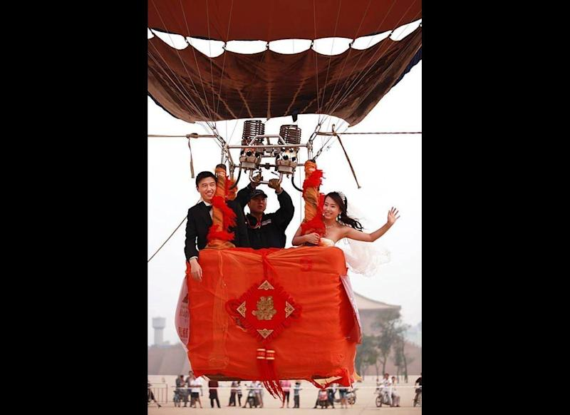 A couple in a hot-air balloon wave to spectators during a sky wedding ceremony at the Daming Palace Ruins Park in Xian of Shaanxi Province, China. Fifteen couples rode in hot-air balloons to celebrate their wedding ceremony. (China Photos / Getty Images)