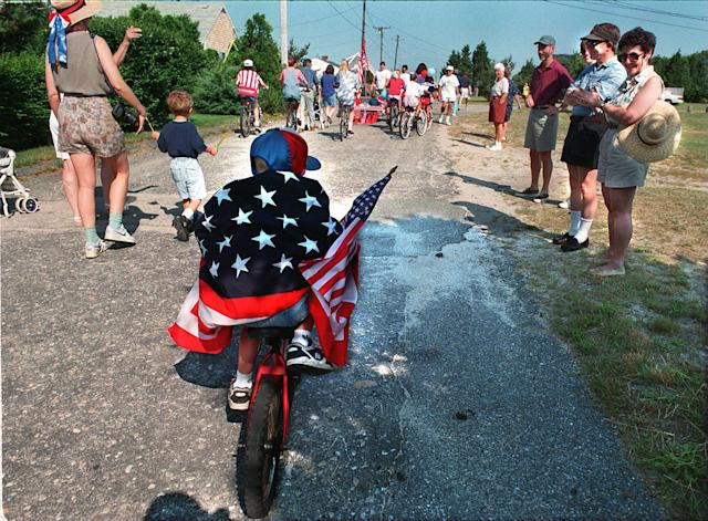 <p>Five-year-old Sean Kennedy in the annual Fourth of July Parade bicycles through the streets of Mashnee, Mass., 1995. (Photo: Suzanne Kreiter/The Boston Globe via Getty Images) </p>
