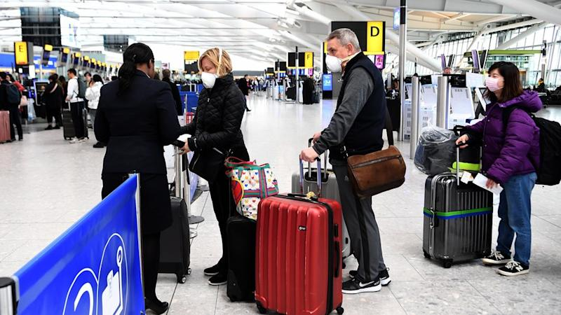 Travellers queue up for flights at Heathrow Airport in London, Britain, 14 March 2020.