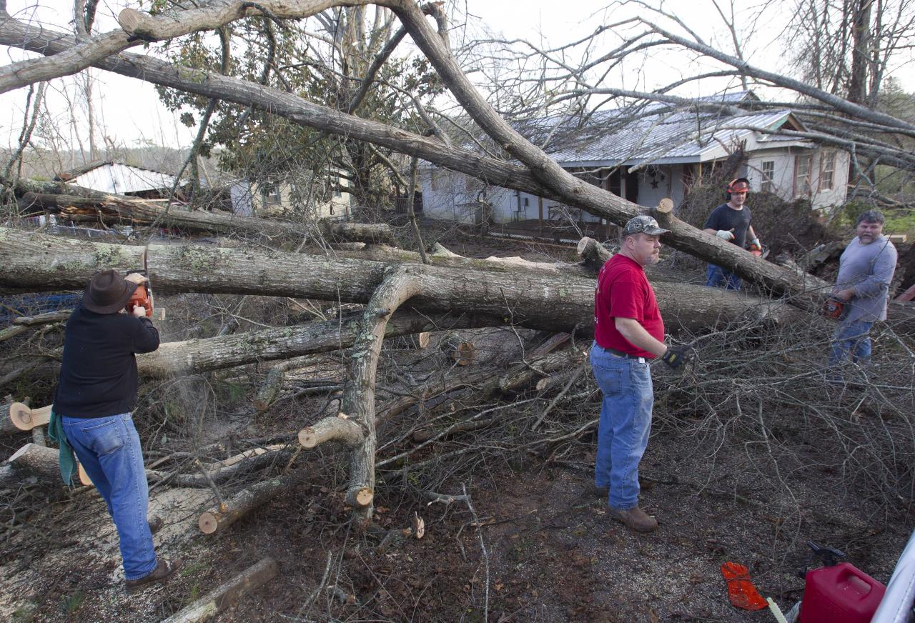 Residents cut fallen trees off of houses in Oak Grove, Ala., Monday, Jan. 23, 2012. after a possible tornado passed through the area. Homes were flattened, windows were blown out of cars and roofs were peeled back in the middle of the night in the community of Oak Grove near Birmingham. (AP Photo/Dave Martin)