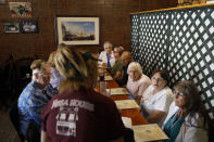 Local residents listen as a waitress takes their order at the Pizza House restaurant one of the oldest restaurants in Galesburg, Ill., Wednesday, June 16, 2021. (AP Photo/Shafkat Anowar)